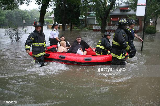Firefighters from the Chicago Fire Department rescue a family on Sunday September 14 in Chicago Illinois after constant rain flooded parts of Albany...