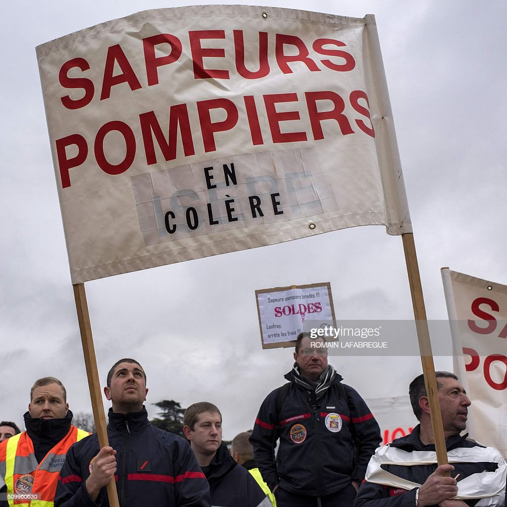 Firefighters from the Drome and 40 other French departments hold a banner reading 'Angry firefighters' as they protest in Valence, central eastern France, on February 13, 2016 against the closure of 19 emergency services and fire centers. / AFP / ROMAIN LAFABREGUE