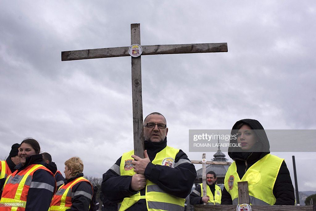 Firefighters from the Drome and 40 other French departments hold a cross as they protest against the closure of 19 emergency services and fire centers, in Valence central eastern France, on February 13, 2016. / AFP / ROMAIN LAFABREGUE