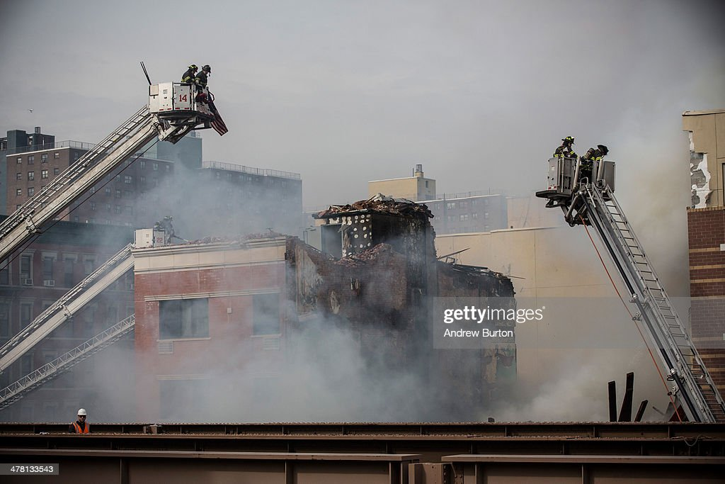 Firefighters from the Fire Department of New York (FDNY) respond to a 5-alarm fire and building collapse at 1646 Park Ave in the Harlem neighborhood of Manhattan March 12, 2014 in New York City. Reports of an explosion were heard before the collapse of two multiple-dwelling buildings that left at least 11 injured.