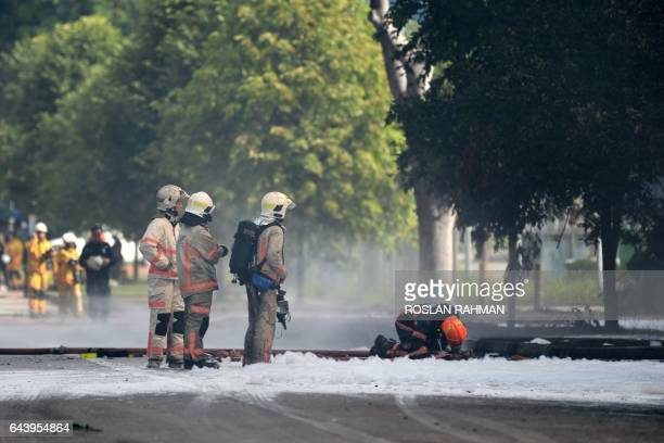 Firefighters from the Singapore Civll Defence Force use foam to extinguish a fire at a waste management plant in Singapore on February 23 2017 About...