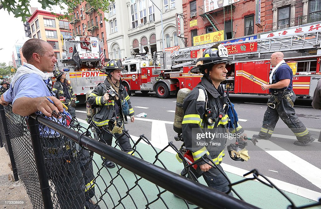 Firefighters gather at the scene of an explosion and partial building collapse in the Chinatown neighborhood on July 11, 2013 in New York City. Seven people were injured in the apparent basement gas explosion in the five-story building in Lower Manhattan.