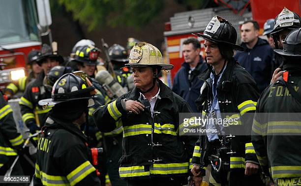Firefighters gather on the street in front of a threealarm fire that broke out at 502 East 14th Street across from Stuyvesant Town in lower Manhattan...