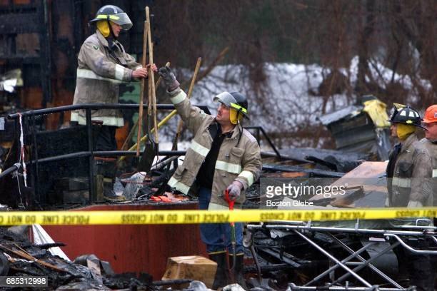 Firefighters gather shovels from the front staircase that were used in the recovery and search operation as they prepared to fence off the scene late...