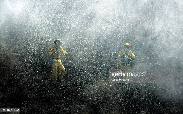 Firefighters get doused with foam from a helicopter while battling a wildfire burning near south Interstate 15 at Lake Street in Lake Elsinore...