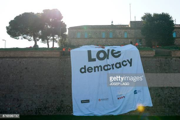 Firefighters hang a giant banner reading 'Love Democracy' at the Montjuic Castle in Barcelona on November 20 2017 during a protest calling for the...