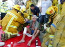 Firefighters help a man injured at the scene of a plane crash at an apartment building June 6 2003 in the Fairfax district of Los Angeles California...