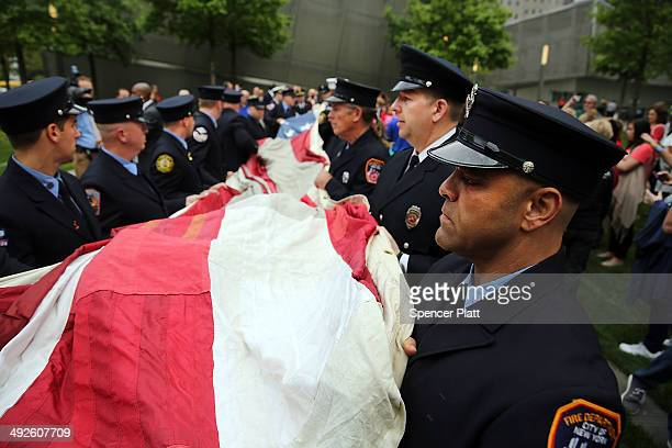 Firefighters help fold the flag as they participate in the ceremonial transfer of the National 9/11 Flag into the The National September 11 Memorial...