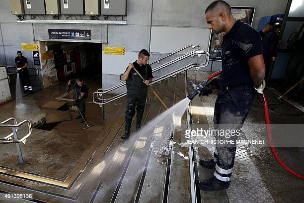 Firefighters help to clean up the train station of Antibes southeastern France on October 5 2015 after floods tore through the French Riviera leaving...