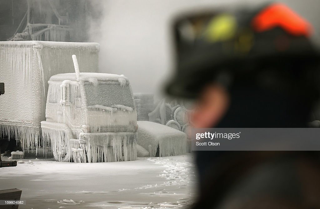 Firefighters help to extinguish a massive blaze at a vacant warehouse on January 23, 2013 in Chicago, Illinois. More than 200 firefighters battled a five-alarm fire as temperatures were in the single digits.