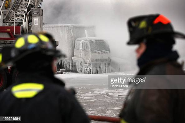 Firefighters help to extinguish a massive blaze at a vacant warehouse on January 23 2013 in Chicago Illinois More than 200 firefighters battled a...