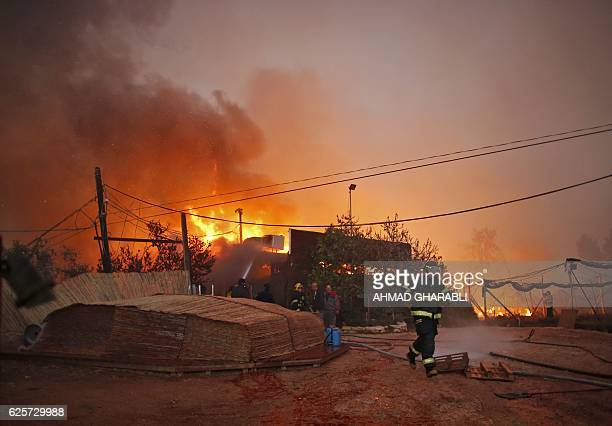 Firefighters helps extinguish a new fire that broke out in the Israeli town of Nataf west of the Arab Israeli town of Abu Ghosh along the border with...