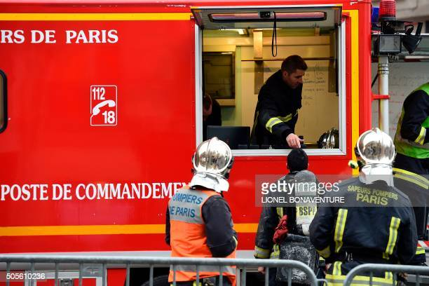 Firefighters hold a briefing while on site outside the Ritz Hotel in Paris to extinguish a fire that erupted at the landmark hotel on January 19 2016...