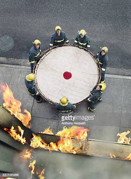 Firefighters holding safety net