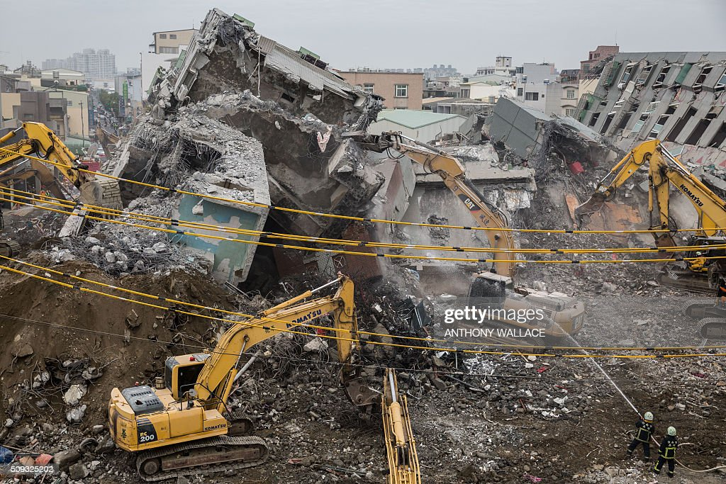 Firefighters (bottom R) hose down falling rubble to prevent dust from rising as excavators are used during the search and rescue operation at the Wei-Kuan complex which collapsed in the 6.4-magnitude earthquake, in the southern Taiwanese city of Tainan on February 10, 2016. Taiwan prosecutors were on February 10 questioning the developer of the apartment complex that collapsed during the earthquake as prosecutors detailed flaws in construction of the building where nearly 100 people remain trapped. AFP PHOTO / ANTHONY WALLACE / AFP / ANTHONY WALLACE