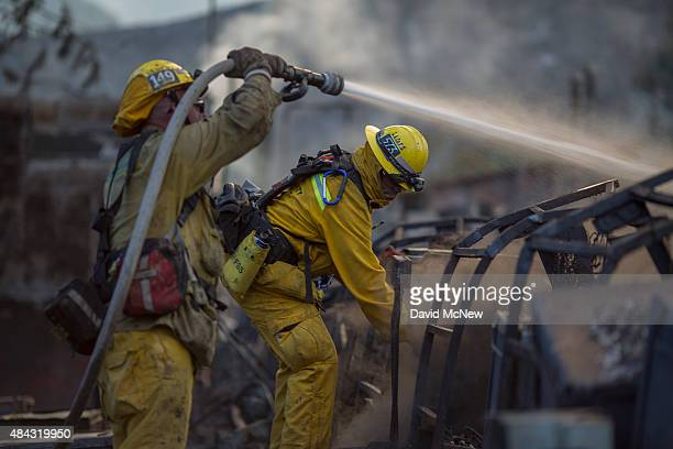 Firefighters hose down the smoldering ruins of a building at the Warm Springs Rehabilitation Center at the Warm Fire on August 16 2015 in the Angeles...