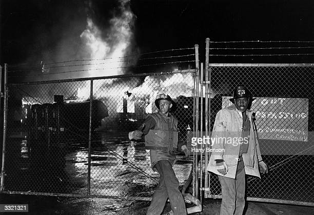 Firefighters in front of a blazing building during the Watts Riots in Los Angeles California 11th15th August 1965