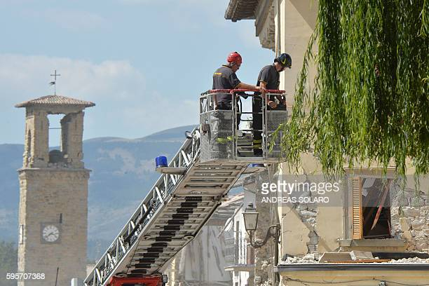 Firefighters inspect a damaged building from the elevated platform of a firetruck in the central Italian village of Amatrice on August 26 two day...