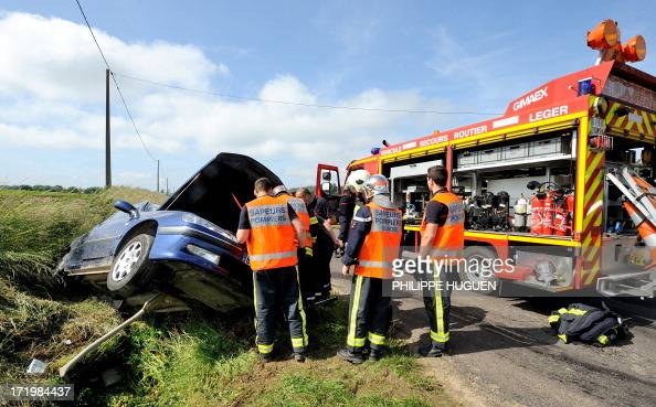 Firefighters inspect a damaged car along a road on June 30 2013 in Godewaersvelde northern France following a traffic accident between two vehicles...