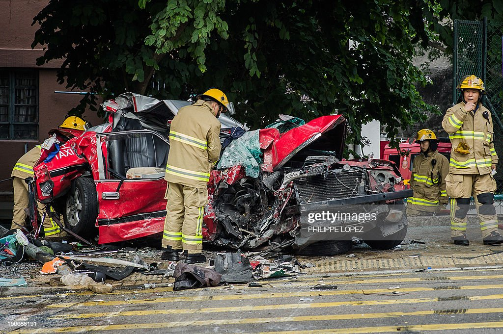 Firefighters inspect a taxi crushed during an accident with two double-decker buses in Hong Kong on November 19, 2012. Three people died and about 50 were injured in the crash which occured in the eastern district of Shau Kei Wan. AFP PHOTO / Philippe Lopez