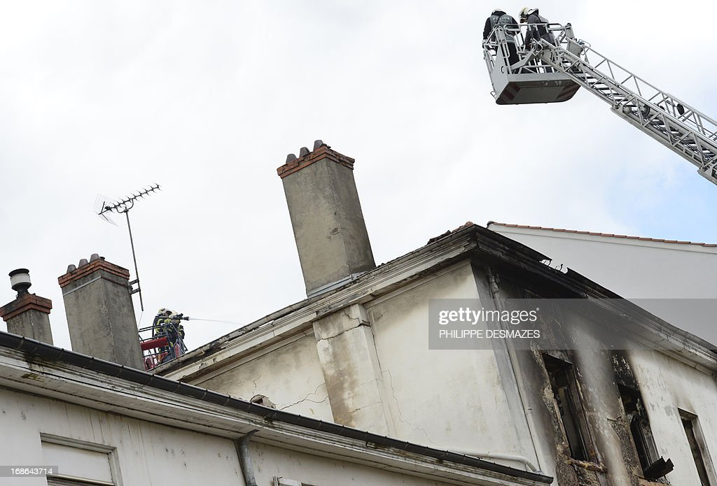 Firefighters inspect an abandoned factory that was housing nearly 300 Roma squatters, which caught fire overnight, killing at least three people, including a child, on May 13, 2013 in the southeastern city of Lyon. AFP PHOTO/PHILIPPE DESMAZES