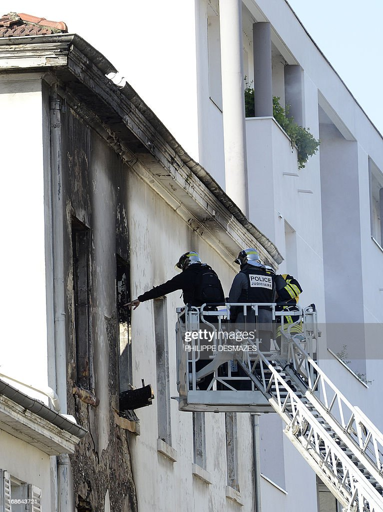Firefighters inspect an abandoned factory that was housing nearly 300 Roma squatters, which caught overnight, killing at least three people, including a child, on May 13, 2013 in the southeastern city of Lyon. AFP PHOTO/PHILIPPE DESMAZES