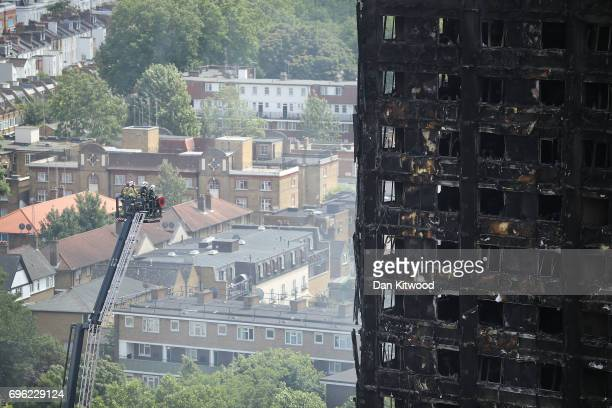 Firefighters inspect the blackened exterior of Grenfell Tower on June 15 2017 in London England At least 17 people have been confirmed dead and...