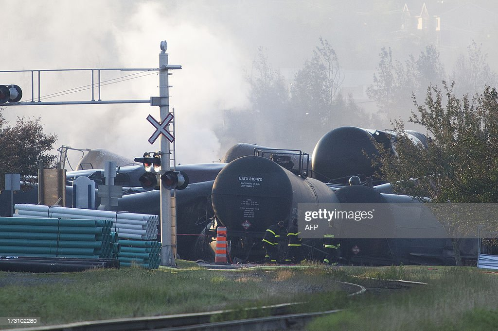 Firefighters inspect the wreckage on July 7 2013 of a freight train loaded with oil that derailed July 6 in LacMegantic in Canada's Quebec province...