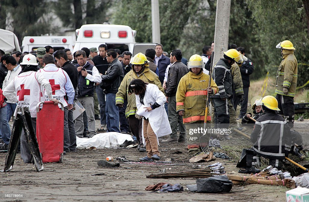 Firefighters, investigators and forensic workers remain around the corpse of one of at least eleven victims of an explosion in Jesusito Nativitas, Tlaxcala, Mexico, on March 15, 2013. A small truck loaded with fireworks for a religious event exploded in central Mexico on Friday, killing at least eleven and injuring dozens, with one witness saying he saw 'bodies flying' as people ran for cover. AFP PHOTO/ Jose CASTANARES