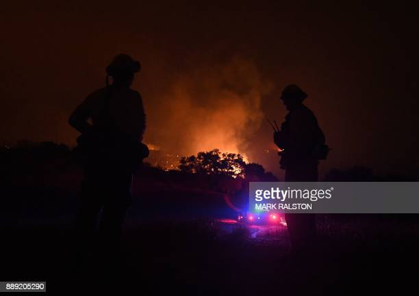 Firefighters keep watch while fire and smoke burns beside a housing estate as the Thomas wildfire continues to burn in Ojai California on December 9...