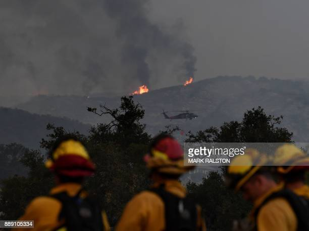 Firefighters keep watch while fire and smoke heads towards their area from the Thomas wildfire in Ojai California on December 9 2017 Brutal winds...