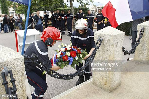 Firefighters lay a wreath of flowers on July 14 2016 in PezillalaRiviere southern France during a ceremony in memory of one of their colleagues who...