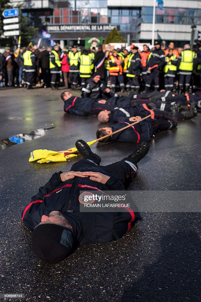 Firefighters lay on the ground during a demonstration in front of the Drome departemental council in Valence, central eastern France, on February 13, 2016, to protest against staffing cuts and the closure of 19 fire stations. / AFP / ROMAIN LAFABREGUE