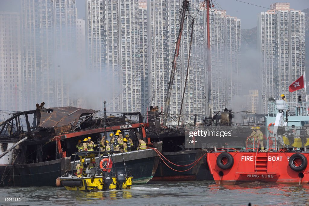 Firefighters (L) load bottles of water onto a fishing vessel as part of their operation to extinguish a fire as their colleagues (R) look on in Hong Kong on January 19, 2013. There were no initial reports of injuries during the incident, which took place in a crowded typhoon shelter. AFP PHOTO / ANTHONY WALLACE