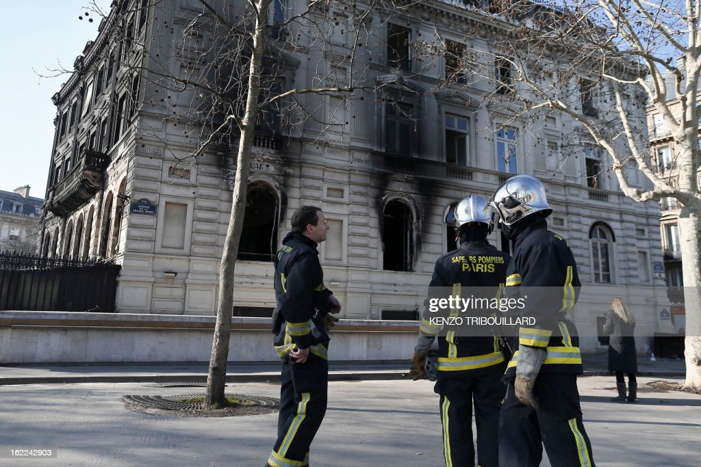 Firefighters look on February 21, 2013 at the damaged building of the Paris nightclub and restaurant L'Arc after a fire, believed to have been set by arsonists, swept through it in the early morning.