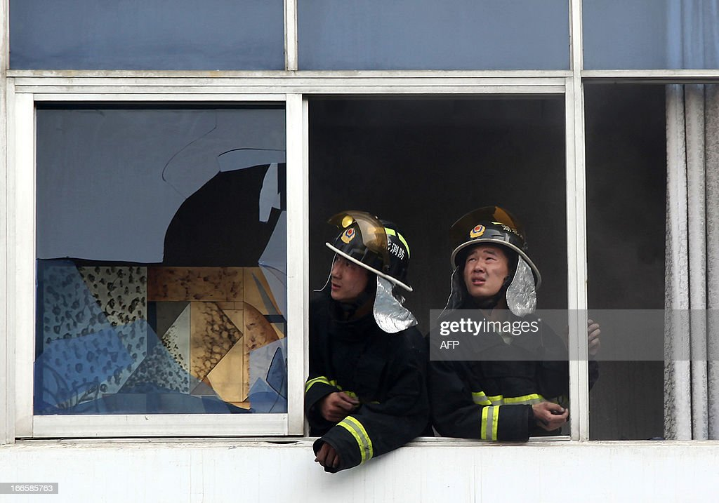 Firefighters look out from a window as they work to put out a fire in a hotel in Xiangyang, central China's Hubei province on April 14, 2013. The fire, started from an Internet cafe downstairs, resulted in 11 deaths and 50 injuries, local government reports annouced. CHINA
