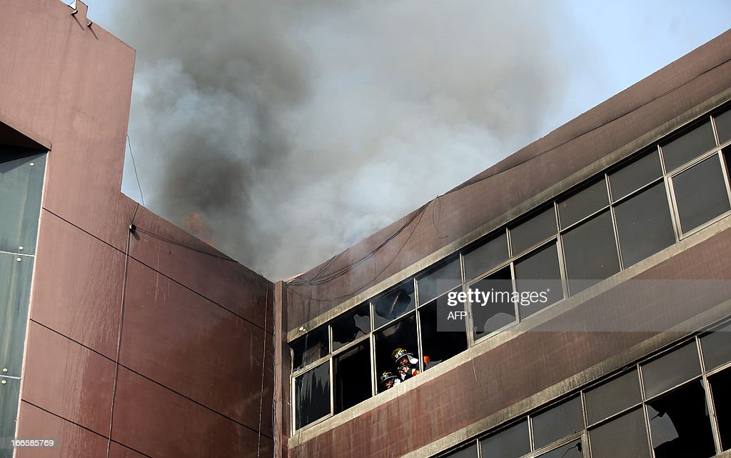 Firefighters look out from a window as they work to put out a fire in a hotel in Xiangyang, central China's Hubei province on April 14, 2013. The fire, started from an Internet cafe downstairs, resulted in 11 deaths and 50 injuries, local government reports annouced. CHINA OUT AFP PHOTO