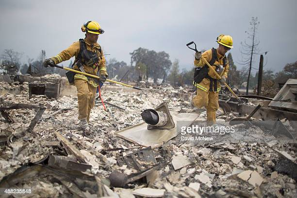Firefighters look through the ruins of structures burned by the Valley Fire on September 14 2015 in Middletown California The 95squaremile fire has...