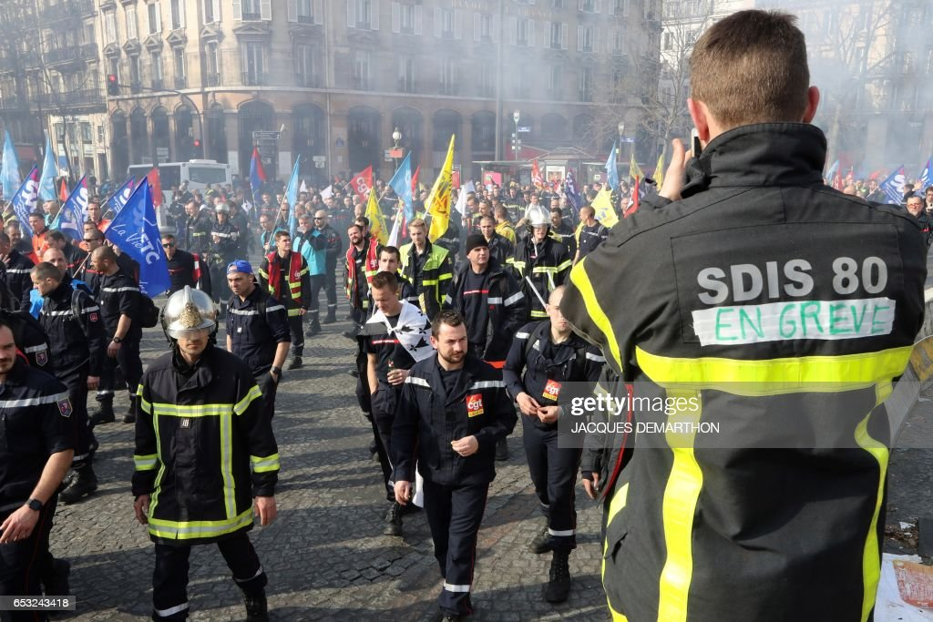 Firefighters march during a demonstration of French firemen against staff reduction on the place de la Bastille in Paris on March 14, 2017. / AFP PHOTO / Jacques DEMARTHON