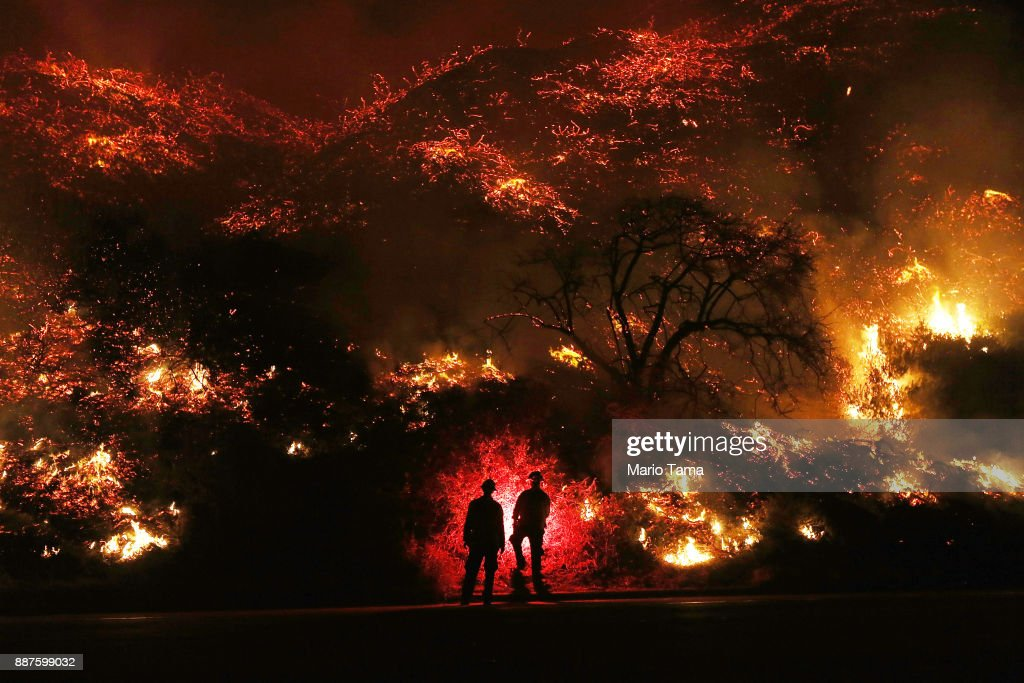 Firefighters monitor a section of the Thomas Fire along the 101 freeway on December 7, 2017 north of Ventura, California. The firefighters occasionally used a flare device to burn-off brush close to the roadside. Strong Santa Ana winds are rapidly pushing multiple wildfires across the region, expanding across tens of thousands of acres and destroying hundreds of homes and structures.
