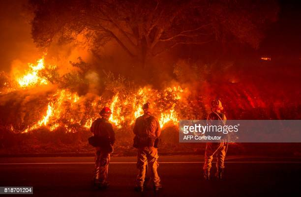 Firefighters monitor flames on the side of a road as the Detwiler fire rages on near the town of Mariposa California on July 18 2017 California has...