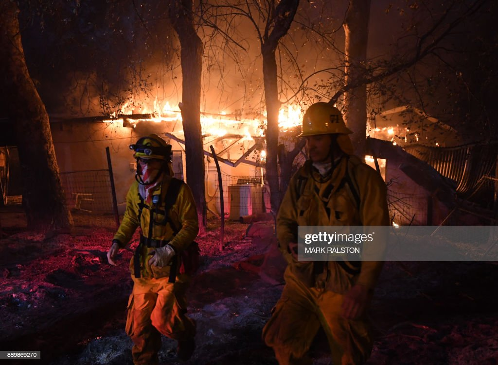 TOPSHOT - Firefighters move away from a burning house after discovering downed live power lines, as the Thomas wildfire continues to burn in Carpinteria, California, on December 10, 2017. The Thomas fire is only 15 percent contained, now threatening the city of Santa Barbara and the nearby coastal town of Carpinteria, making it one of the worst wildfires in California history. RALSTON