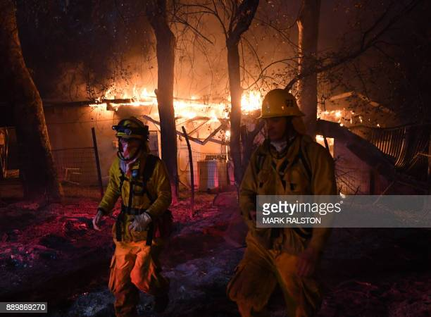 TOPSHOT Firefighters move away from a burning house after discovering downed live power lines as the Thomas wildfire continues to burn in Carpinteria...