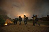 Firefighters of the Texas Canyon Hotshot crew fight the Sand Fire at a residential golf course on July 23 2016 near Santa Clarita California Fueled...