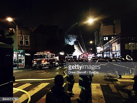 Firefighters On City Street In City At Night