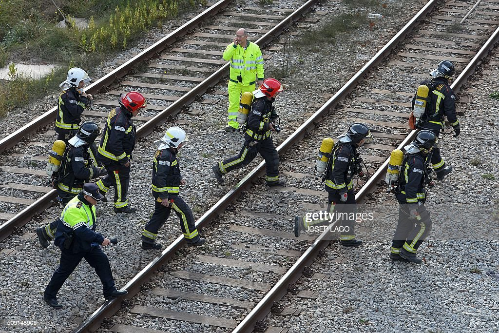Firefighters operatE along railway tracks following a fire at an abandoned train station in Barcelona on February 9, 2016. Barcelona's railway network was brought to a standstill for several hours today affecting some 72,000 passengers during rush hour after a fire brokeout in an unused train station. / AFP / JOSEP LAGO