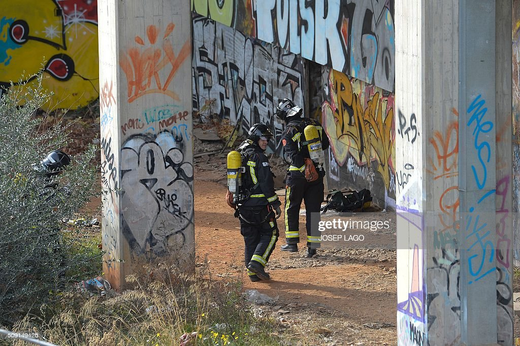 Firefighters operate next to an entrance for an abandoned underground station where a fire brokeout in Barcelona on February 9, 2016. Barcelona's railway network was brought to a standstill for several hours today affecting some 72,000 passengers during rush hour after a fire brokeout in an unused underground station. / AFP / JOSEP LAGO