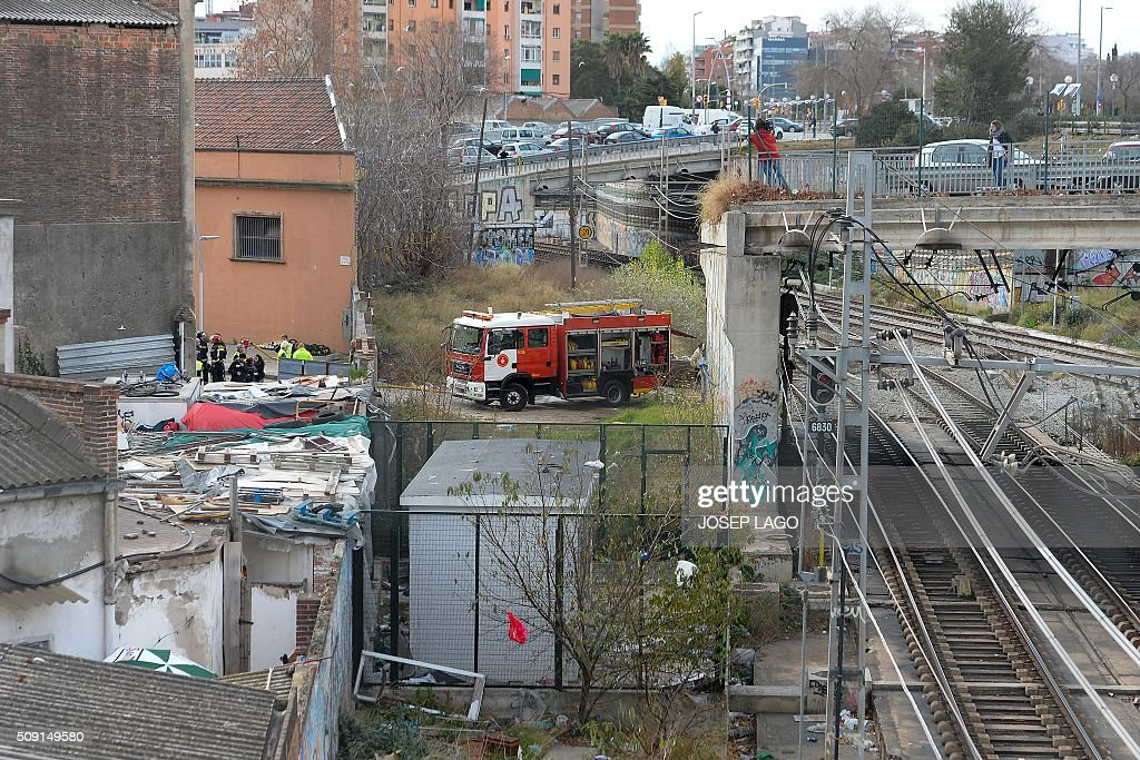 Firefighters operate next to railway tracks following a fire at an abandoned underground station in Barcelona on February 9, 2016. Barcelona's railway network was brought to a standstill for several hours today affecting some 72,000 passengers during rush hour after a fire brokeout in an unused train station. / AFP / JOSEP LAGO