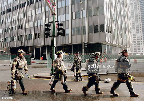 Firefighters pack up after extinguishing a fire in the former Chicago SunTimes newspaper building December 29 2004 in Chicago Illinois The building...