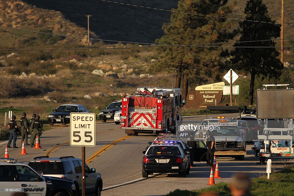 Firefighters pass a roadblock on Highway 38 toward the Big Bear Lake as a standoff with the ex Los Angeles police officer believed to now be a quadruple murder suspect Christopher Dorner continues with the cabin he is believed to be in burning, near San Bernardino, California, on February 12, 2013, some 46 miles (75 km) from the San Bernardino Mountains near Big Bear where Dorner, a former Los Angeles, has barricaded himself in a cabin and exchanged gunfire with police who have the cabin surrounded. AFP PHOTO / David McNew